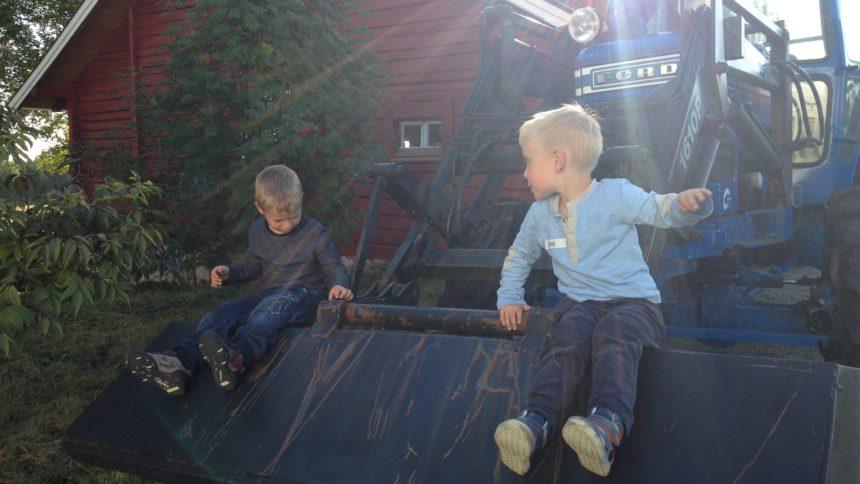 Bildet viser to små gutter som sitter på en traktor